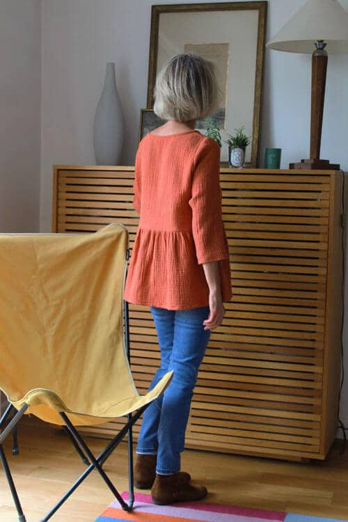 Femme de dos portant une blouse en tissu aérien de couleur brique
