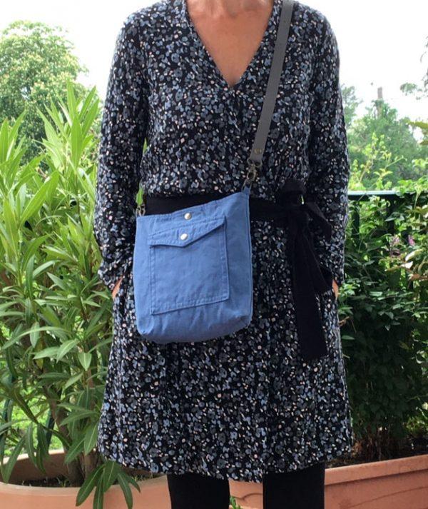 Femme portant un sac bleu indigo format besace Reine de Bohème en coton/lin recyclé et toile à matelas, bandoulière en veau grainé