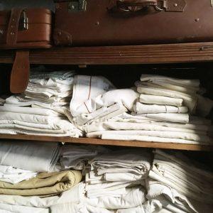 Armoire de brocante remplie de draps anciens